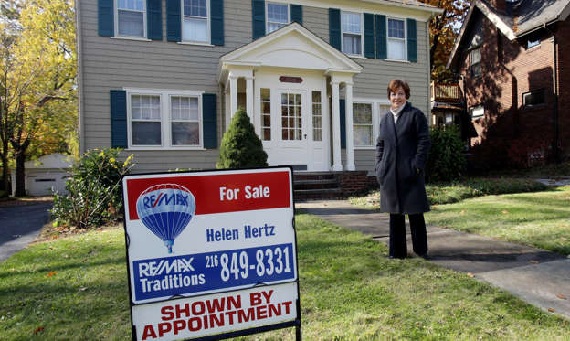 Slide 1 of 51: Realton Helen Hertz stands in front of one of her listings in Cleveland Heights, Ohio Friday, Oct. 24, 2014. Hertz, a real estate agent for more than three decades, has seen firsthand what has happened to the market in the wake of the recession and foreclosure crisis.