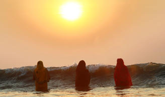 Women offer prayers as the sun sets over the Arabian Sea during Chhath Puja festival in Mumbai.