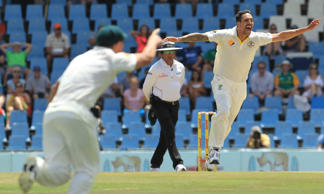 File: Australia's bowler Mitchell Johnson, right, celebrates his wicket as umpire Aleem Dar, center, of Pakistan watches on the fourth day of their their cricket test match against South Africa at Centurion Park in Pretoria, South Africa