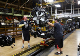 Chrysler Group assembly workers lower an engine onto the frame of a 2014 Ram 150...