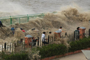 A group of tourists narrowly avoid being washed away by a monster tidal wave on Qiantang River, Zhejiang, China.