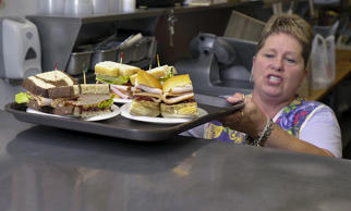 Goldie Gordios calls out the sandwich orders to people chosing to eat inside at the Full Belly Deli at Pine Tree Shopping Center, Tuesday, October 23, 2012. They include the Fall Fowl, Hamwich and Perkey Turkey.