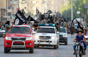 File photo of militant Islamist fighters waving flags, travel in vehicles as they take part in a military parade along the streets of Syria's northern Raqqa province.