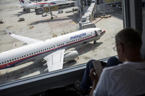 A man looks at a notepad as an aircraft operated by Malaysian Airline System Bhd. stands on the tarmac at Kuala Lumpur International Airport in Sepang, Malaysia, on Tuesday, Aug. 26, 2014.