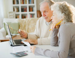 Senior couple going over paperwork with laptop