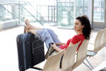 Woman sitting with luggage in airport lounge