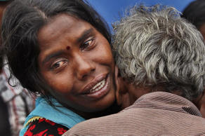 A Sri Lankan mudslide survivor, left, who lost her two daughters is comforted by her father.