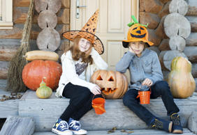 Children in front wooden door decorated for Halloween