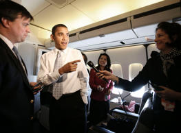 U.S. President Barack Obama speaks to the press as he walks through the press cabin aboard Air Force One.