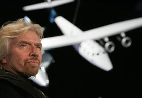 Sir Richard Branson, founder of Virgin Galactic, with a scale model of the Spaceship Two.