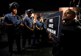 A protester demonstrates in front of a police line in Ferguson, Missouri October 10, 2014.