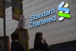 An illuminated logo sits on display outside a bank branch of Standard Chartered Plc