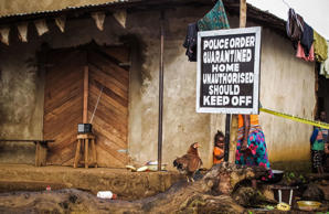 A child stands near a sign advising of a quarantined home in Port Loko, Sierra Leone.