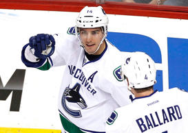 Vancouver Canucks' Alexandre Burrows (L) celebrates with teammate Keith Ballard after scoring a second period goal over the Colorado Avalanche in their NHL hockey game.