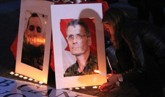 A woman light candles during a candlelight vigil to honour the memory of the fallen Canadian soldiers, Warrant Officer Patrice Vincent and Corporal Nathan Cirillo in Montreal, October 28, 2014.