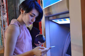 Young woman checking receipt at cash machine