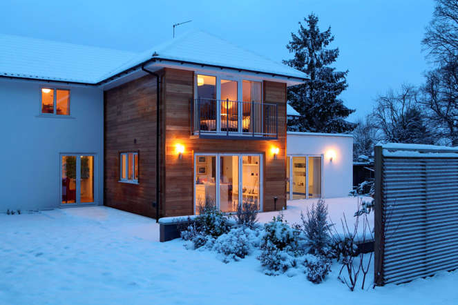 Illuminated family home in snow