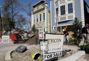 In this Feb. 22, 2010 photo, builders complete new homes  in Houston. One home is for sale and the other has been sold. New home sales sink 2.2 percent to record low amid stormy weather, weak economy.(AP Photo/Pat Sullivan)