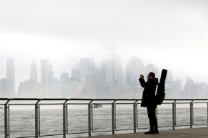 Richard Espinal, of New York City, pauses during his walk to work as a music instructor to photograph the fog blanketing New York City, Wednesday, Nov. 12, 2014, from the Hudson River front in Hoboken, N.J. The National Weather Service said the fog reduced visibility to a quarter mile or less. Motorists were advised to slow down.