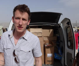 In this undated file photo provided by his family, Peter Kassig stands in front of a truck filled with supplies for Syrian refugees.