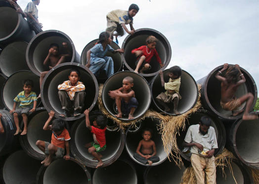 Slide 1 of 17: Children play in water pipes at a construction site on the banks of the Yamuna River in the northern Indian city of Allahabad in 2010.