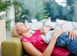 Mother and child sleeping on a couch