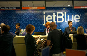 Passengers check-in for at a JetBlue Airways counter October 24, 2014 in Long Beach, California.