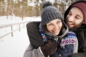 Smiling couple hugging in snow