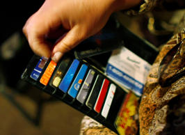 A woman looks in her wallet for credit cards.