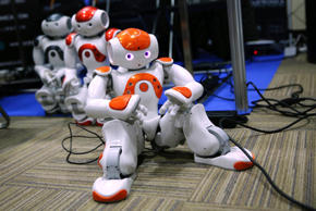 Humanoid robots sit on the floor during the International Conference on Humanoid Robots in Madrid November 19, 2014.