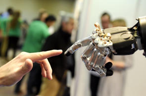 A man moves his finger toward SVH (Servo Electric 5 Finger Gripping Hand) automated hand made by Schunk during the 2014 IEEE-RAS International Conference on Humanoid Robots in Madrid on November 19, 2014. The conference theme 'Humans and Robots Face-to-Face' confirms the growing interest in the field of human-humanoid interaction and cooperation, especially during daily life activities in real environments.