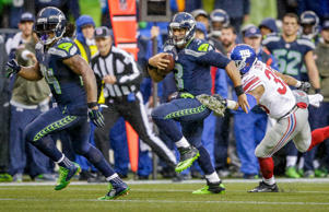 Seattle Seahawks running back Marshawn Lynch looks to block for quarterback Russell Wilson as Wilson runs against the New York Giants in the second half of an NFL football game, Sunday, Nov. 9, 2014, in Seattle.