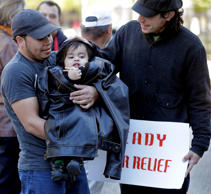 Denis Cherino, of Honduras, holds his 17-month-old son, also named Denis, wrapped in his coat, along with Arnulfo Manriquez, right, as immigrants and activists hold a protest outside the U.S. Citizenship & Immigration Service office in New Orleans, Wednesday, Nov. 19, 2014.