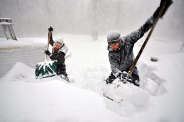 Tami Normile and Richard Brooks attempt to remove some of the five feet of snow from a roof top on November 20, 2014 in the Lakeview neighborhood of Buffalo, New York. The record setting Lake effect snowstorm dumped up to six feet of snow in less than 24 hours closing a one hundred mile section of The New York State Thruway as well as other major roads around Buffalo. Seven deaths have already been  attributed to the storm and a second round beginning late Wednesday evening will bring up to three more feet of snow overnight and into Thursday.