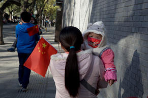 Visitors to the forbidden city carry children holding the Chinese national flags in Beijing, China, Nov. 16, 2013.