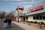 Two men walk toward a Darden Restaurants Inc. Red Lobster location in Peoria, Illinois, U.S., on Tuesday, March 18, 2014.