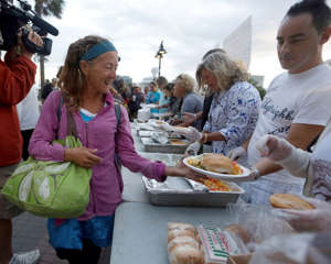 Suzanne Haines Walsh, 60, who is homeless, left, gets a meal from volunteers working with homeless advocate Arnold Abbott, at a public parking lot next to the beach, Wednesday, Nov. 5, 2014, in Fort Lauderdale, Fla.