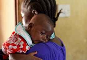 A baby naps on his mother's shoulder as they enter the vaccination room during a routine visit at the Kuntorloh Community Health Center in the outskirts of Freetown on November 14, 2014. Ebola-hit Sierra Leone faces social and economic disaster as gains made since the country's ruinous civil war are wiped out by the epidemic, according to a major study.