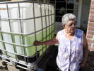 In this photo taken Monday, Sept. 15, 2014, Vickie Yorba, 94, stands next to a water tank in front of her home in East Porterville, Calif., where she has lived for 66 years. Hers is one of 290 East Porterville wells that ran dry in the state's historic drought. Since February, she has had to rely on friends, relatives and charities for water to drink and bathe.