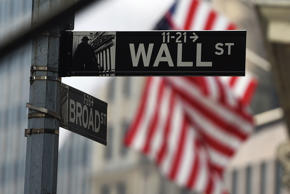 A Wall Street sign is pictured in the rain outside the New York Stock Exchange in New York June 9, 2014.