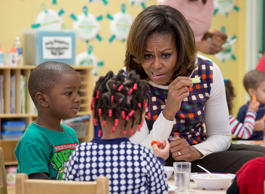 First lady Michelle Obama eats healthy snacks with children during a visit to La Petite Academy in Bowie, Md., Thursday, Feb. 27, 2014, to promote healthy environments and encouraging healthy habits at preschools as part of her Let's Move! Child Care program.