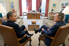 United States President Barack Obama meets with former President George H. W. Bush in the Oval Office.
