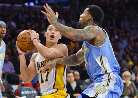 Los Angeles Lakers guard Jeremy Lin (17) drives on Denver Nuggets forward Wilson Chandler (21) as he goes to the basket in the first half of an NBA basketball game, Sunday, Nov. 23, 2014, in Los Angeles.