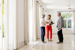 Older couple talking with woman in large living space.
