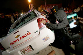 A group of protesters vandalize a police vehicle after the announcement of the grand jury decision not to indict police officer Darren Wilson in the fatal shooting of Michael Brown, an unarmed black 18-year-old, Monday, Nov. 24, 2014, in Ferguson, Mo.
