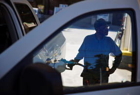 In this Oct. 30, 2014 photo, Joe Warner fills up his tank at a gas station in Atlanta.