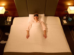 Woman sleeping in middle of double bed in hotel, wearing sleeping mask.