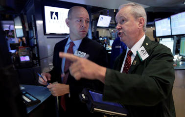 Specialist Jay Woods, left, and trader James Riley work on the floor of the New York Stock Exchange on Monday.