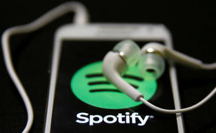 Earphones are seen on top of a smartphone with a Spotify logo on it.