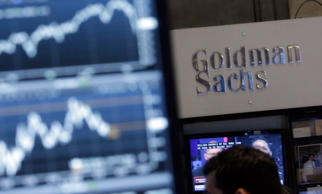 A screen at a trading post on the floor of the New York Stock Exchange is juxtaposed with the Goldman Sachs booth on Oct. 16.